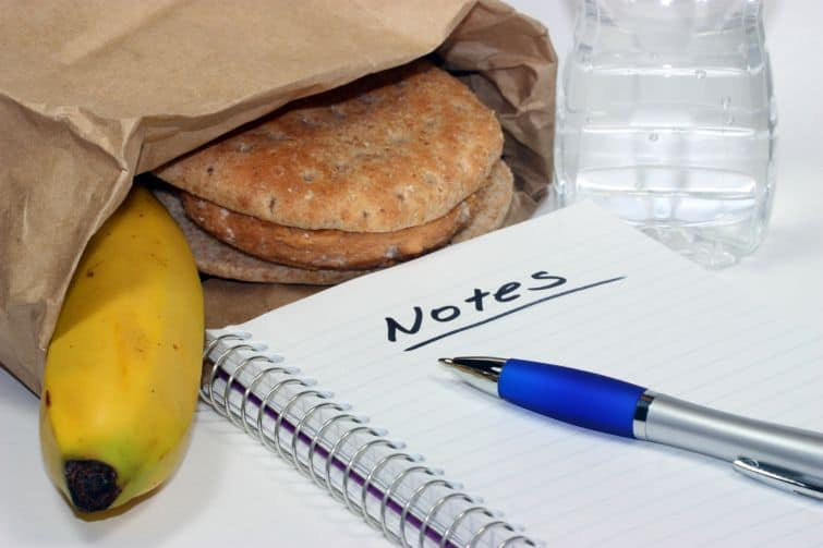 sandwich and banana in lunch bag with notepad and pen for what to bring on a personal retreat