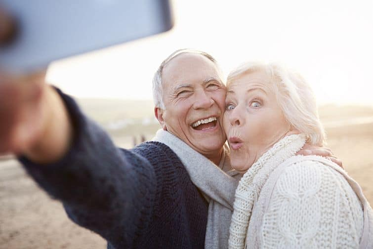 Senior Couple enjoying a long happy life Standing On Beach Taking Selfie