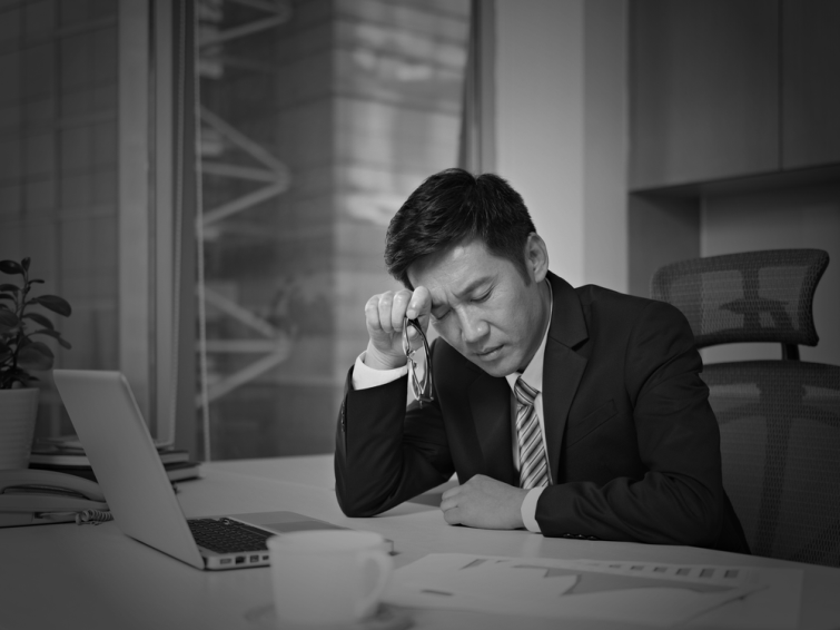 Man in an office looking frustrated and lost with his eyes closed sitting at a desk