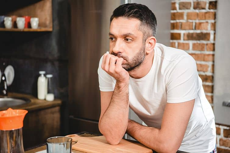 Man in kitchen resting chin on hand leaning over countertop looking thoughtful at his own honesty