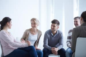 People talking in circle during small group coaching meeting