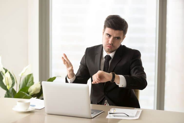 Stressed businessman looking at wrist watch and worrying because of lack of time, late on business meeting, failing deadline. Tired and frustrated office worker nervous after too long day at work. hate what you're good at