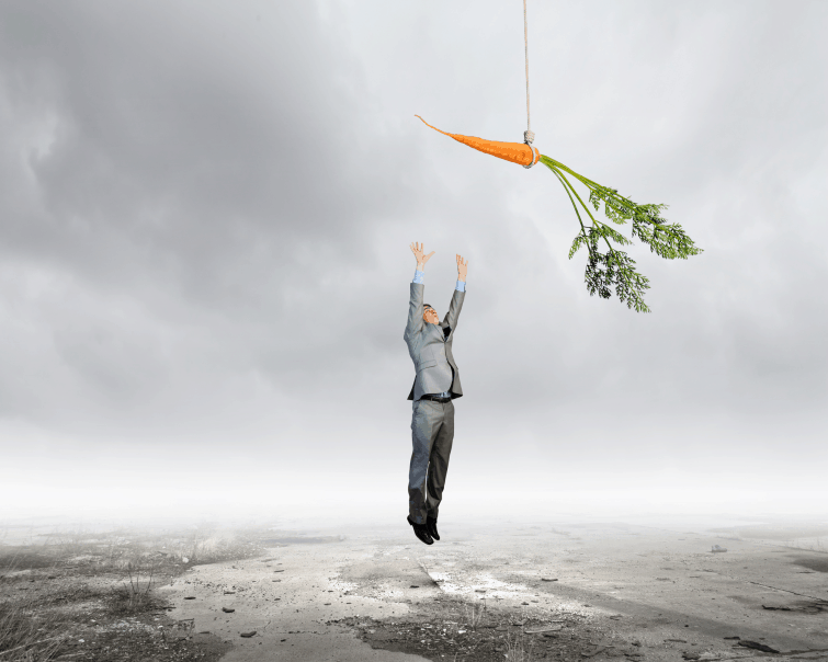 man leaping into the air to reach a carrot indicating his desire to increase motivation